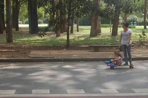 Eine junge Mutter mit Tochter auf einem Skateboard