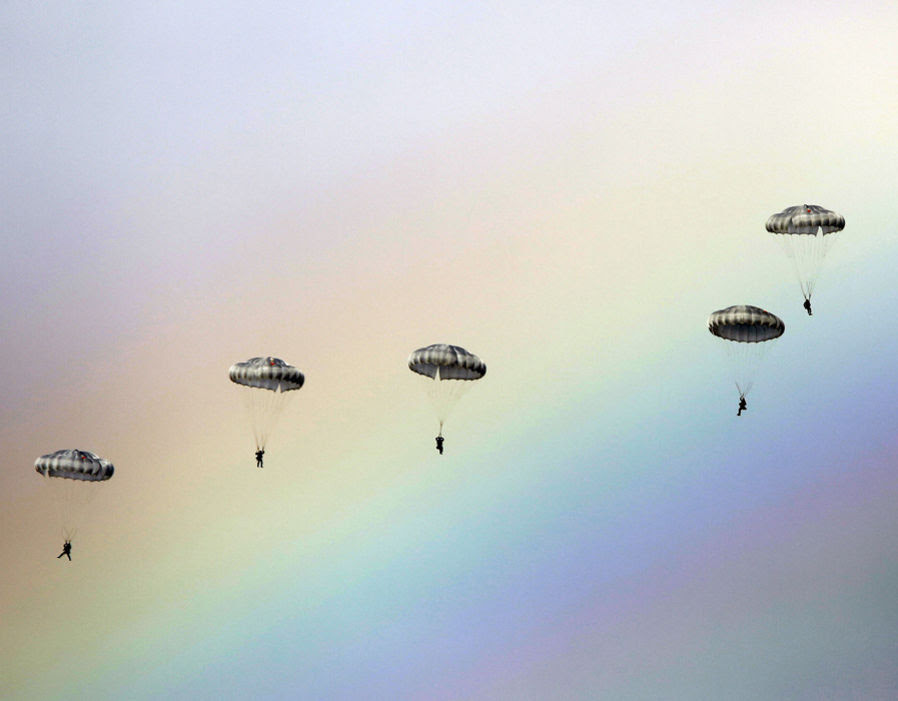 Russian paratroopers jump as a rainbow appears in the sky during the joint Russian, Belarusian and Serbian military exercise