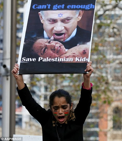A young girl shouted passionately as she held a sign calling for the government to 'save Palestinian kids'
