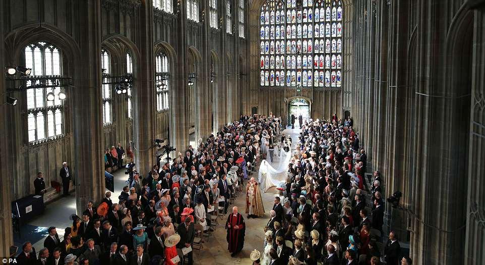 Meghan Markle e seu grupo de noivos caminham com ela pelo altar da Capela de São Jorge, no terreno do Castelo de Windsor