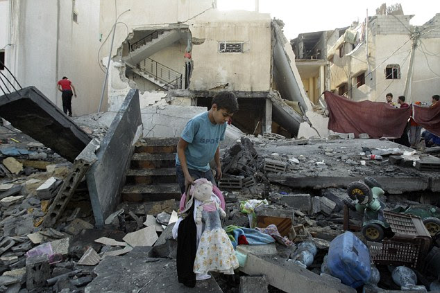 Destroyed: A Palestinian boy holds a doll as he walks amid the rubble of a destroyed house after what witnesses said was an Israeli air strike, in Rafah in the southern Gaza Strip