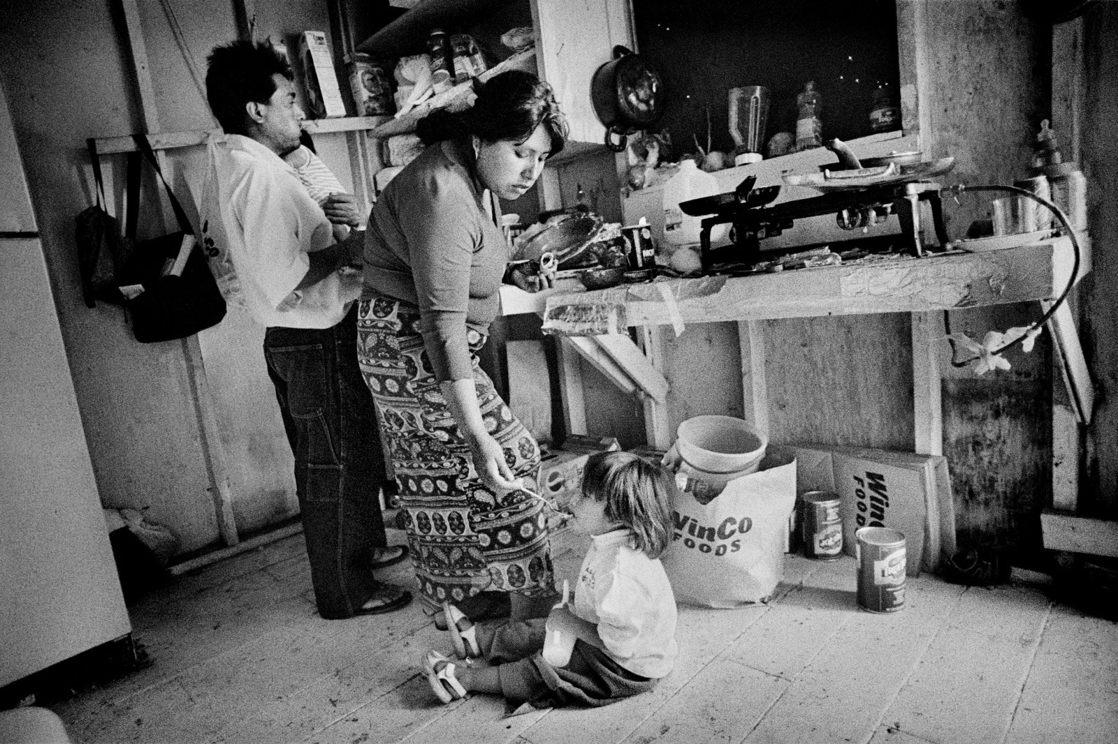 A Oaxacan immigrant mother feeds her daughter in a migrant worker's cabin. Hillsboro, Oregon.