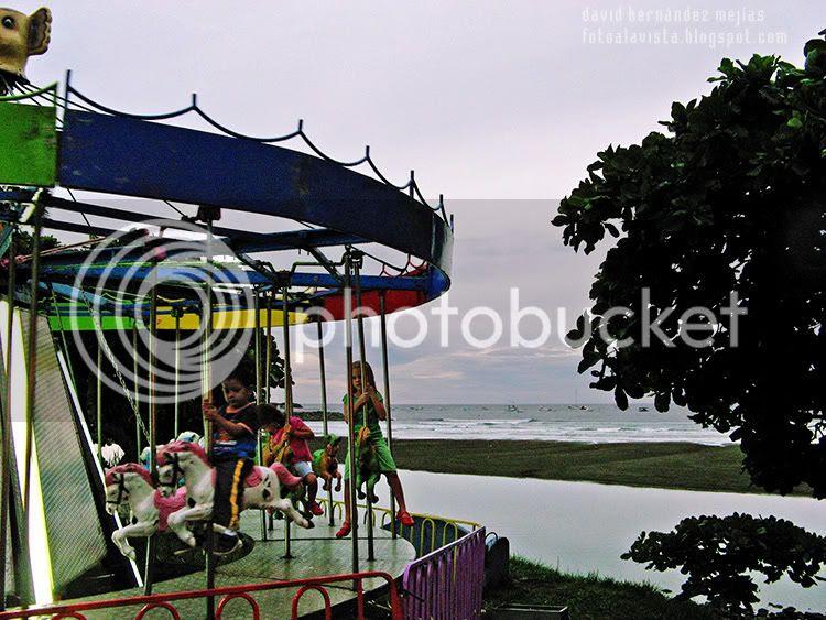 Niños montando en los caballitos a orillas del mar