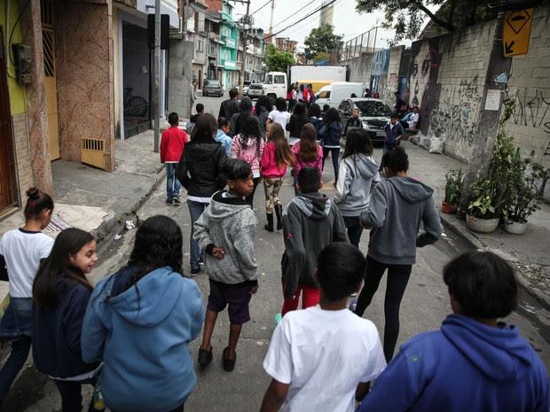 Alunos que participam do projeto 'Caminhos da Arte' andam por rua do Parque Vila Maria em direção ao ônibus que os levará no passeio até o MIS (Foto: Fábio Tito/G1)
