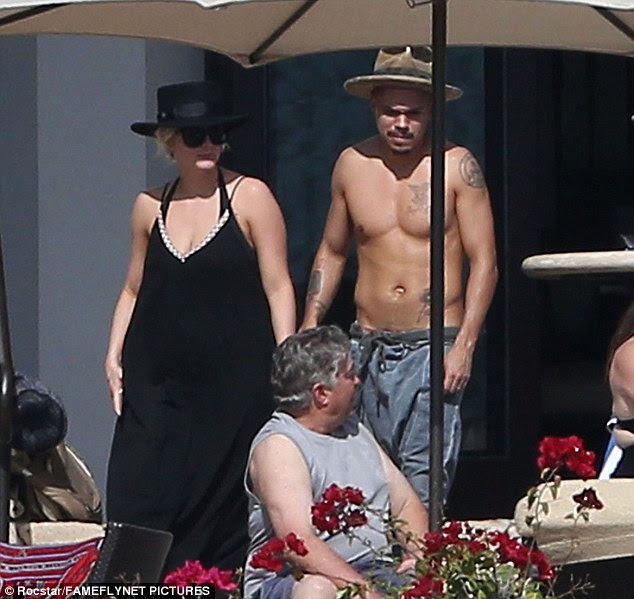 Concealed: Ashlee  kept covered in a full-length black maxi dress with matching trilby