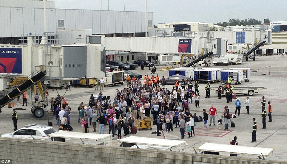 People stand on the tarmac at the Fort Lauderdale-Hollywood International Airport
