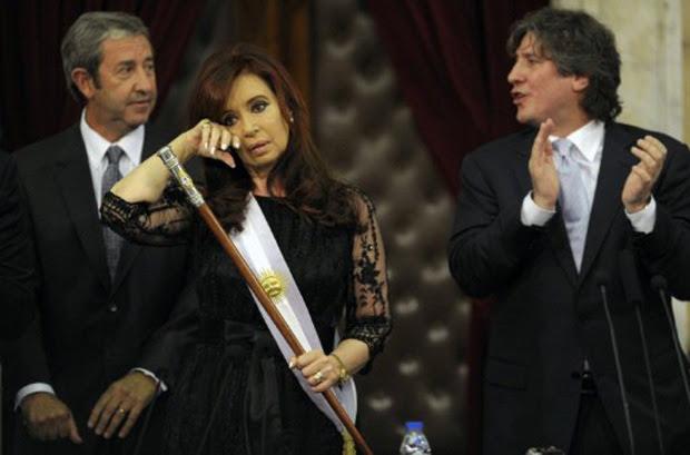 Cristina Kirchner chora após receber a faixa presidencial, entre o ex-vice-presidente Julio Cobos (esq) e o atual, Amado Boudou (dir) (Foto: Juan Mabromata/ AFP)