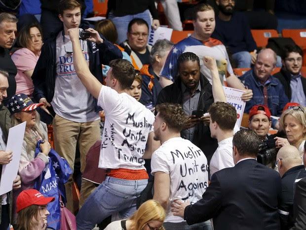 Manifestantes com camisetas com os dizeres 'muçulmanos unidos contra Trump' saem de local de comício de Donald Trump após brigas entre apoiadores e opositores (Foto:  REUTERS/Kamil Krzaczynski)