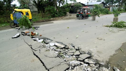Véhicules passent des fissures sur une route qui est apparue le long de la route nationale à la ville de Rizal après un tremblement de terre a frappé la ville de Surigao, le sud des Philippines Février 11, 2017.