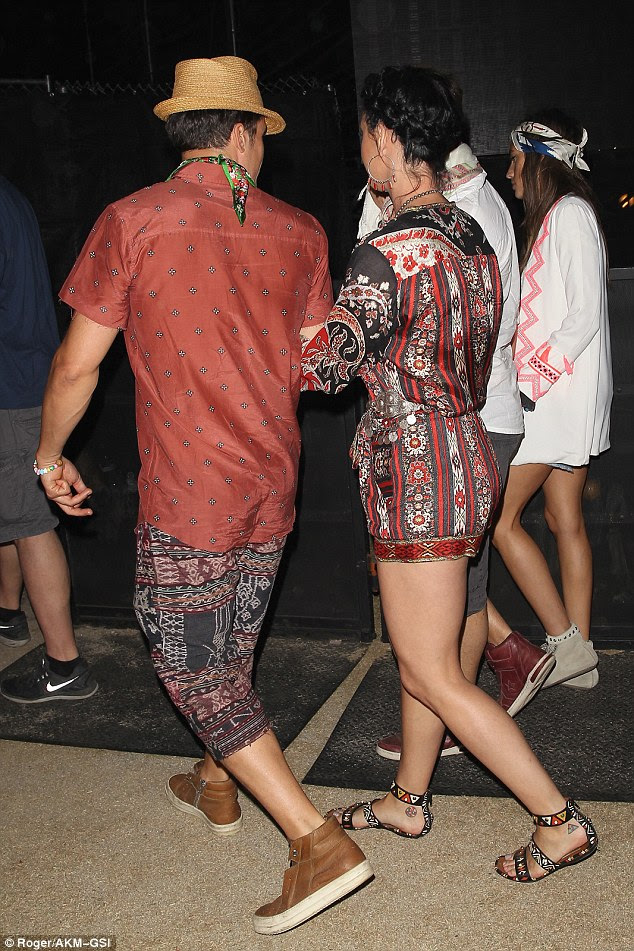 Legs be having you: Katy rocked a paisley playsuit, making the most of her generous assets and her long, tanned legs while Orlando rocked a shirt and Aztec shorts in a similar pattern