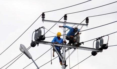 Dua petugas PT PLN tengah melakukan perbaikan jaringan listrik.