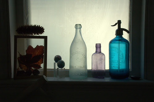 Still-life with bottles, leaves, pinecone and marbles on windowsill