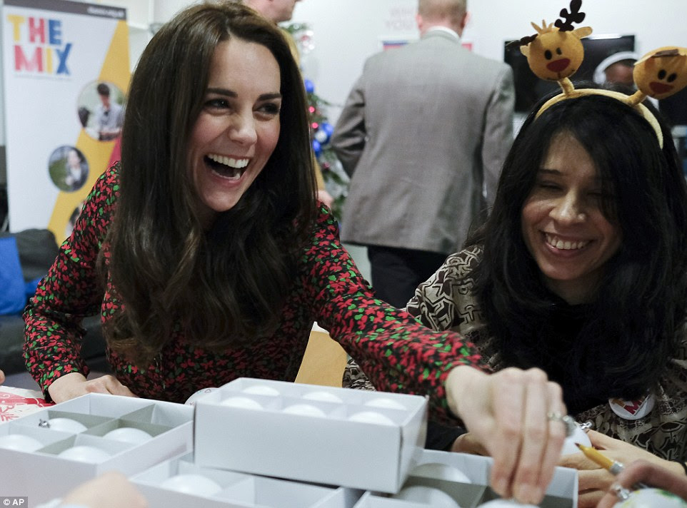 Kate, The Duchess of Cambridge, left, smiles and gestures as she talks to staff and young people, during a visit a visit to The Mix in London
