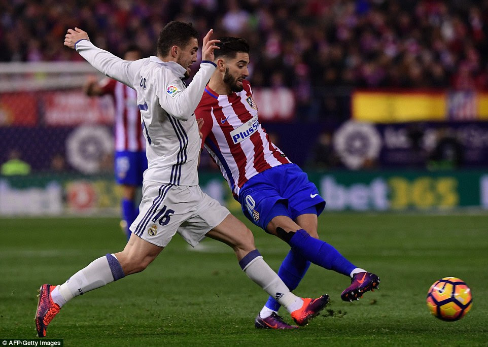 Real Madrid midfielder Mateo Kovacic looks to steal the ball as Atletico's Yannick Carrasco attempts to make a pass