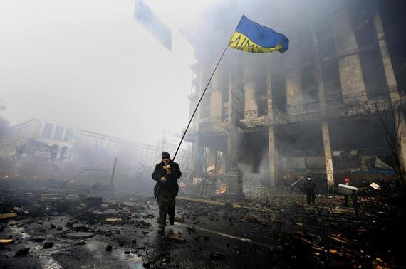 An anti-government protester holds a Ukranian flag as he advances through burning barricades in Kiev's Independence Square February 20, 2014. REUTERS-Yannis Behrakis