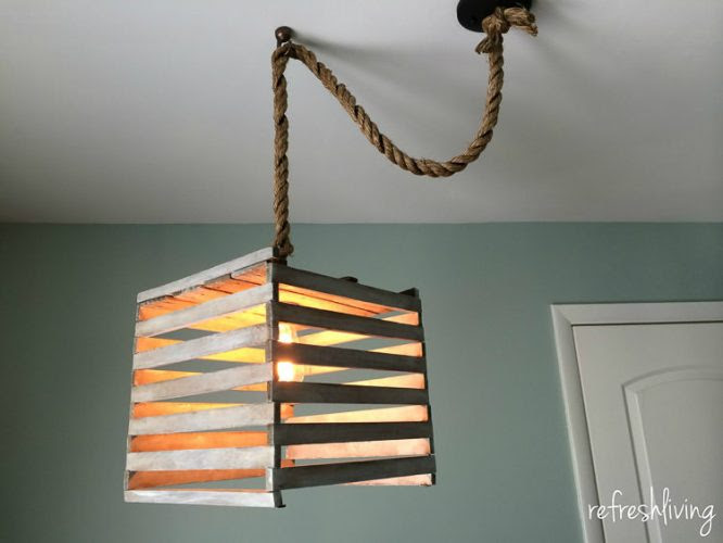 Farmhouse style light fixture made from an antique egg crate. It's easy to make using a pendant light kit and a simple white technique.
