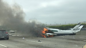 Drew Hoffman drove past a small plane that crashed on the 405 near John Wayne Airport in Santa Ana, California, on Friday.