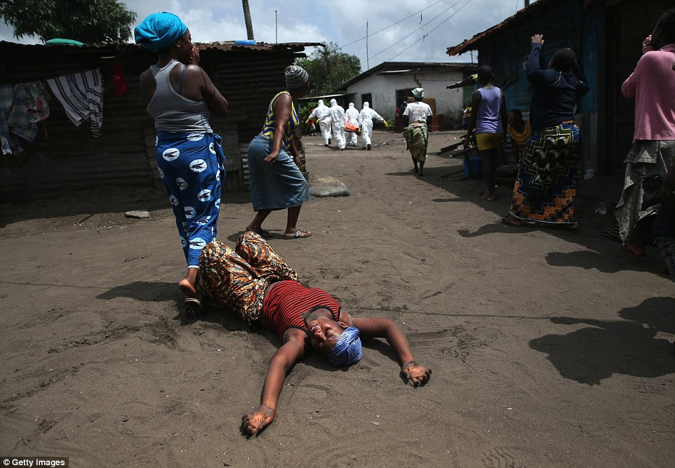 Distraught: The woman's sister, a market vendor, collapsed and died outside her home in Monrovia, Liberia,  while leaving to walk to a treatment center, according to her relatives. Above, the woman is seen grieving on the ground following the burial team's departure