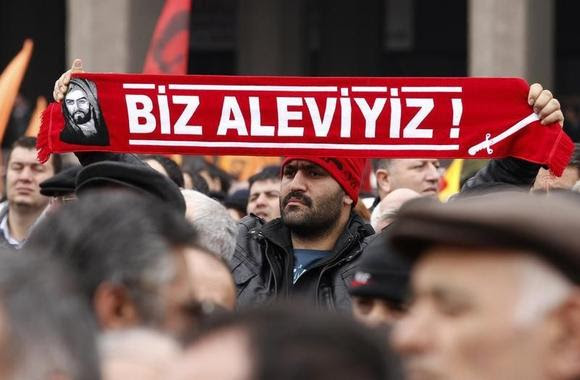 A protester holds a banner reading ''we are alevi'' as he and many others wait to hear the decision of the court in front of a courthouse in Ankara March 13, 2012. REUTERS/Umit Bektas