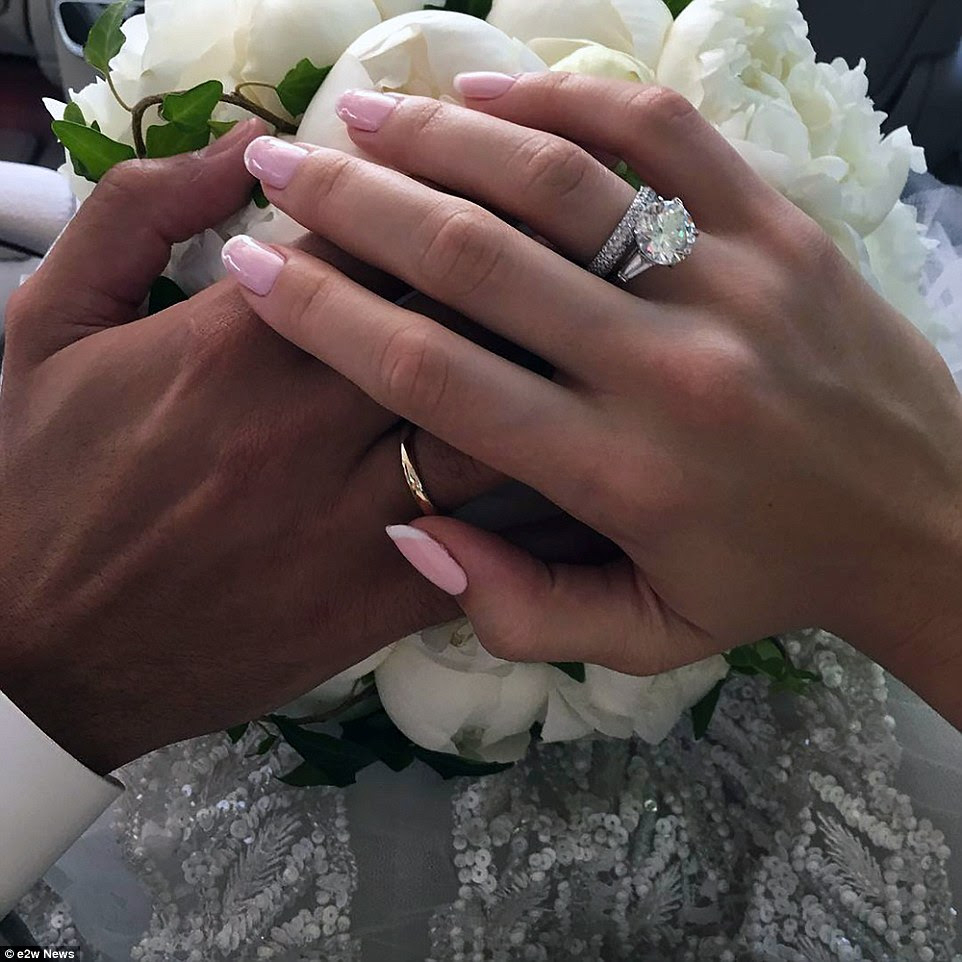 The bride and groom held hands. The ring was described as an 'impressive' diamond ring while her designer dress cost $5000