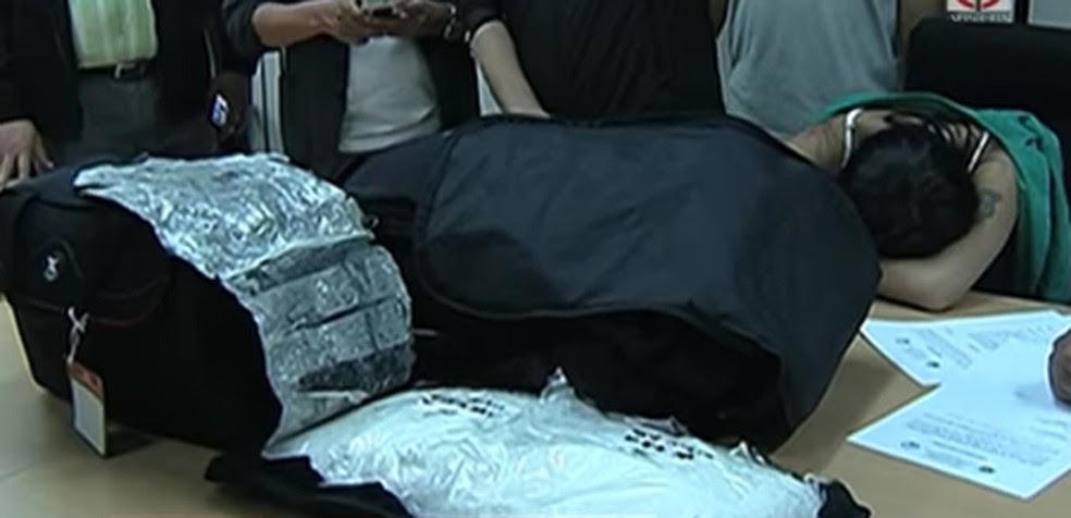 A droga estava escondida em um travesseiro preto, segundo a polícia filipina; ao fundo, Yasmin debruçada na mesa (Foto: Reprodução/ABS-CBN News)