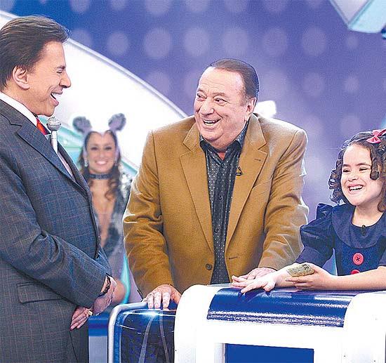 """Raul Gil e a menina Maísa participam do quadro Jogo das 3 Pistas, no """"Programa Silvio Santos"""" (SBT)"""