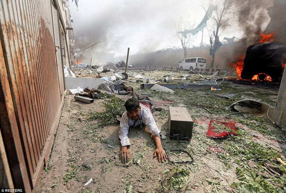 A wounded man lies on the ground at the site of a blast in Kabul, Afghanistan, on May 31. At least 90 were killed in the blast near the German embassy and more than 460 were injured in the car explosion