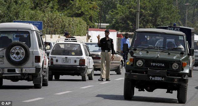 Road patrol: A Pakistani police officer gestures to stop a car at a checkpoint on a road leading to the house where Bin Laden was killed on May 1