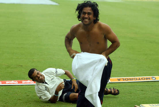 Slide 10 of 46: Indian cricketer Mahendra Singh Dhoni (R) runs back to the shelter of the dressing room after joking with teammate Sreesanth in the rain at the ground as the start of play was delayed by rain on the fourth day of the second test between India and West Indies at the Beausejour stadium in Gros Islet, St. Lucia 13 June 2006. West Indies put to follow-on by India are 43 runs for the loss of 1 wicket after play was called off due to rain.