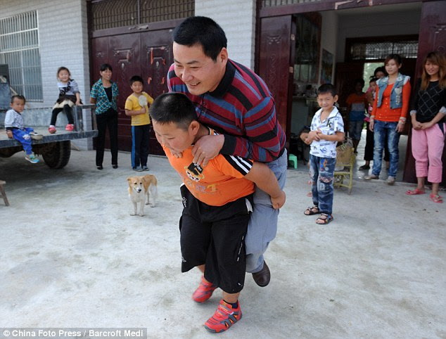 You're meant to give ME the piggyback, dad! The little boy lugs his father around to the bemusement of everyone - including a pet dog