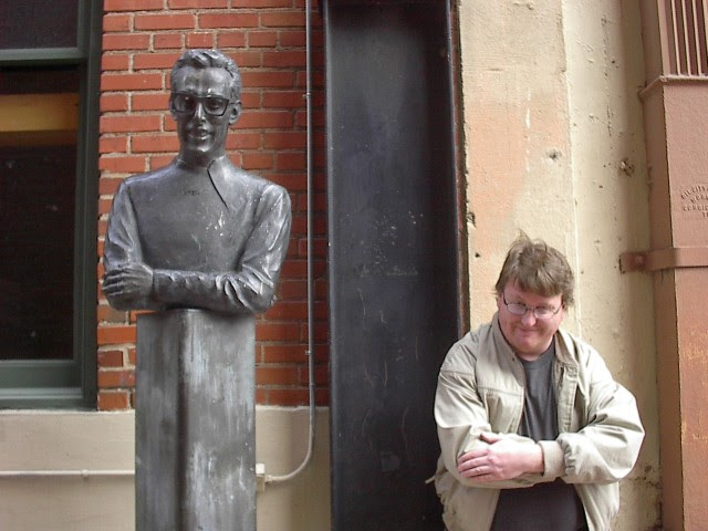 A picture of me next to a bust of Buddy Holly.