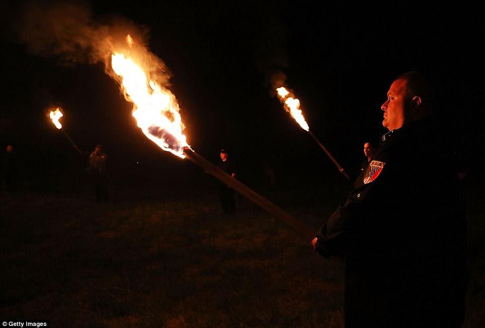 Un miembro del Movimiento Nacional Socialista sostiene una antorcha encendida en preparación para incendiar las esvásticas