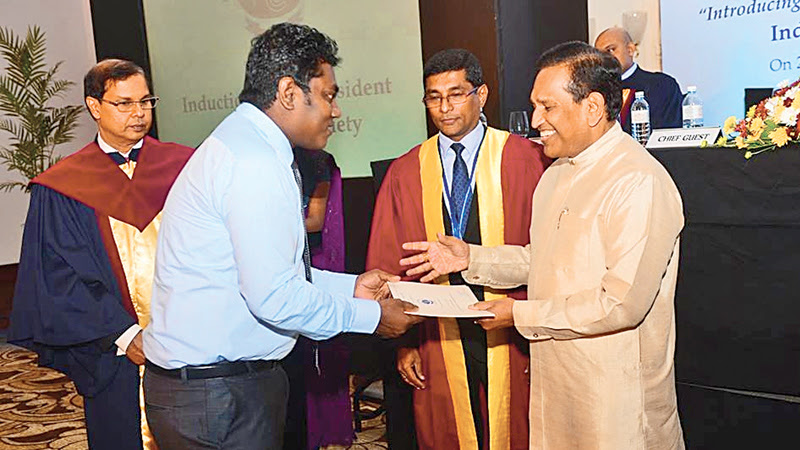 Health Minister Dr.Rajitha Senaratne hands over a certificate to a doctor while Dr.Kapila Jayaratne and Dr.U.A.T.Ratnasiri look on.