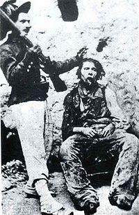 """Nola, 10 settembre 1863, un bersagliere mostra il cadavere del """"brigante"""" Nicola Napolitano dopo la fucilazione e le sevizie"""