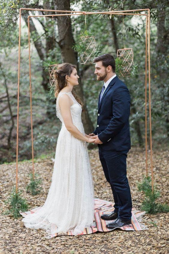 eine kupferne Hochzeit Bogen mit grün dekoriert und geometrische Hänger mit laub