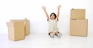 Little boy in a room of moving boxes with hands up