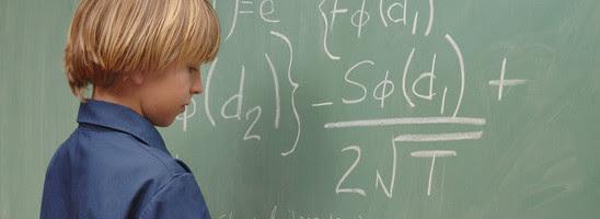 Nine year old boy doing advanced math on a chalkboard