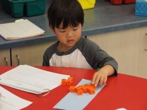 Transitional kindergartener Noah Chang uses manipulatives to solve a math problem during an assessment at Cumberland School in Sunnyvale.