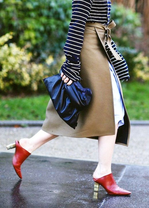 Le Fashion Blog Street Style Spring Layered Look Oversize Stripe Top Brown Apron Wrap Over A Blue Skirt Black Leather Clutch Red Mule Heels Via Refinery29