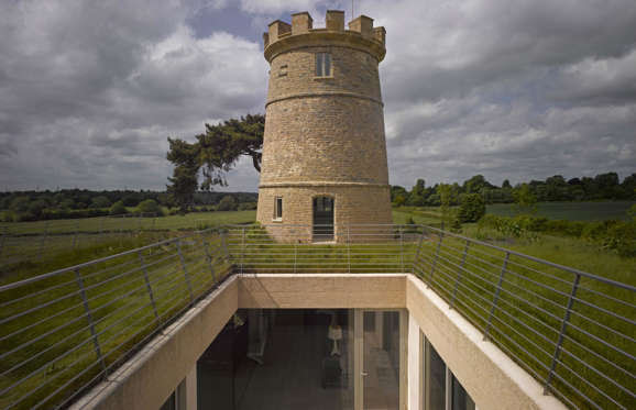 The Round Tower, designed by London-based architects De Matos Ryan, is built into the crest of a hill in the heart of the Cotswolds, England, after it had previously been reduced to ruin.