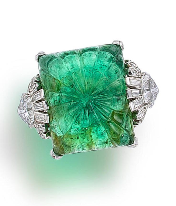 An art deco emerald and diamond ring, circa 1925  centering a rectangular carved emerald with baguette, single, triangular and fancy-shaped diamond shoulders, completed by a plain mount; estimated total diamond weight: 2.70 carats; mounted in platinum;