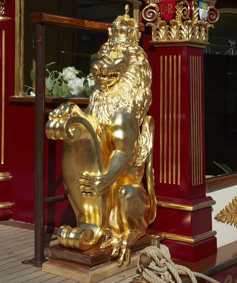 Roaring success: One of the gilded lions guarding the entrance to the coach