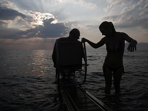 Lefteris Theofilou, que sofre de paraplegia, é ajudado pela mulher, Eleni, de 37 anos, que tem paralisia cerebral (Foto: Yorgos Karahalis/Reuters)