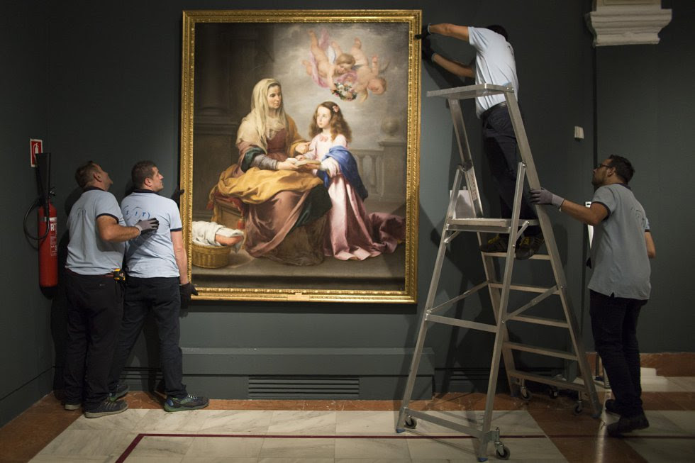 Colocación de la obra de Murillo 'Santa Ana enseñando a leer a la Virgen', en la pared de la Fundación Focus de Sevilla.
