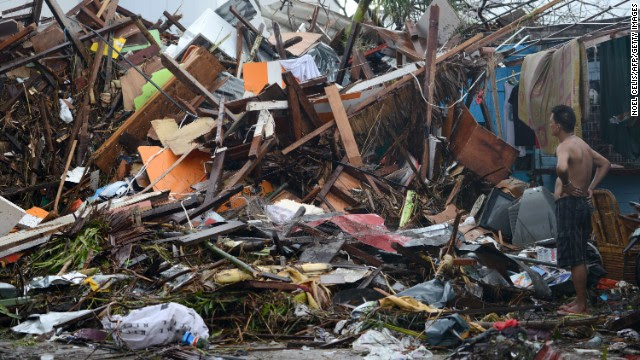 A man looks at the wreckage of destroyed houses in Tacloban on November 10, 2013.