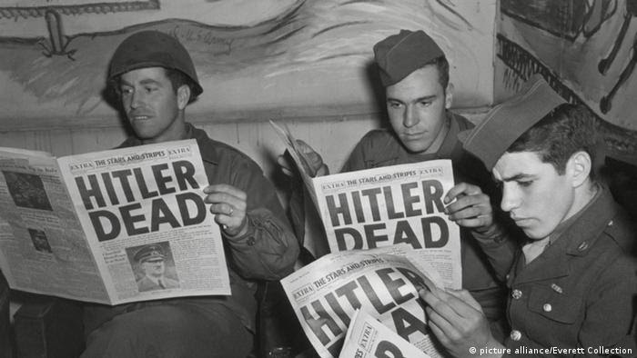 Soldiers reading newspapers with Hitler Dead headline (Foto: picture alliance/Everett Collection)