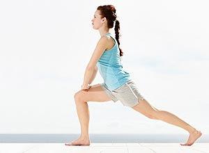 Exercício de agachamento lateral; um apoio, como um cabo de vassoura, pode ajudar a dar mais equilíbrio