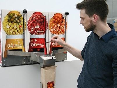 man trekt aan een hendel van een tomatenautomaat die lijkt op een kauwgomballenautomaat