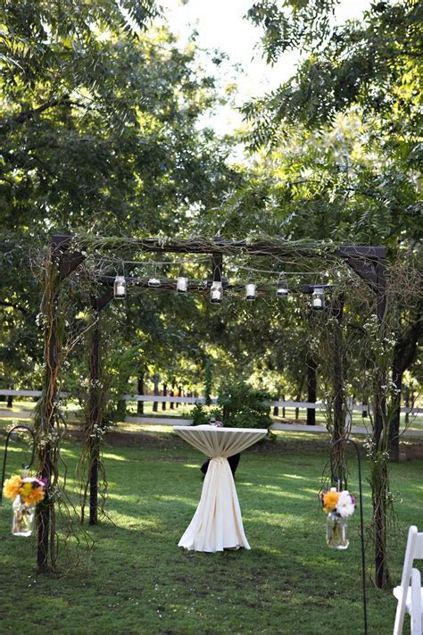 Arbor decorated with mason jars, ivy, & branches. Simply