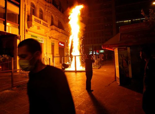 Greek civilian walks pass flames burning in Athens amid unrest aimed at stopping the imposition of further austerity measures designed to stave off the capitalist economic crisis. Parliament voted in favor of further measures against workers and youth. by Pan-African News Wire File Photos